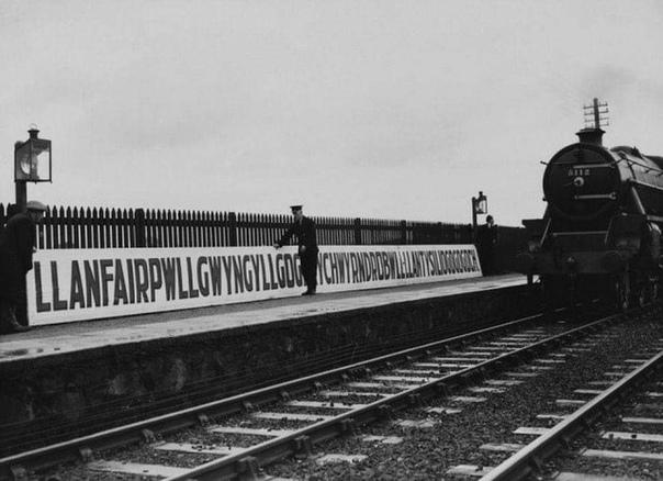 Установка таблички на железнодорожной станции Лланфайрпуллгвингиллгогерыхверндробуллллантисилйогогогох в Уэльсе, Великобритания. Первая половина XX века.