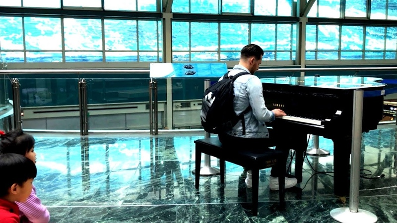 Passenger sits down and plays piano piece at the - YVR (Canadian) Public Airport