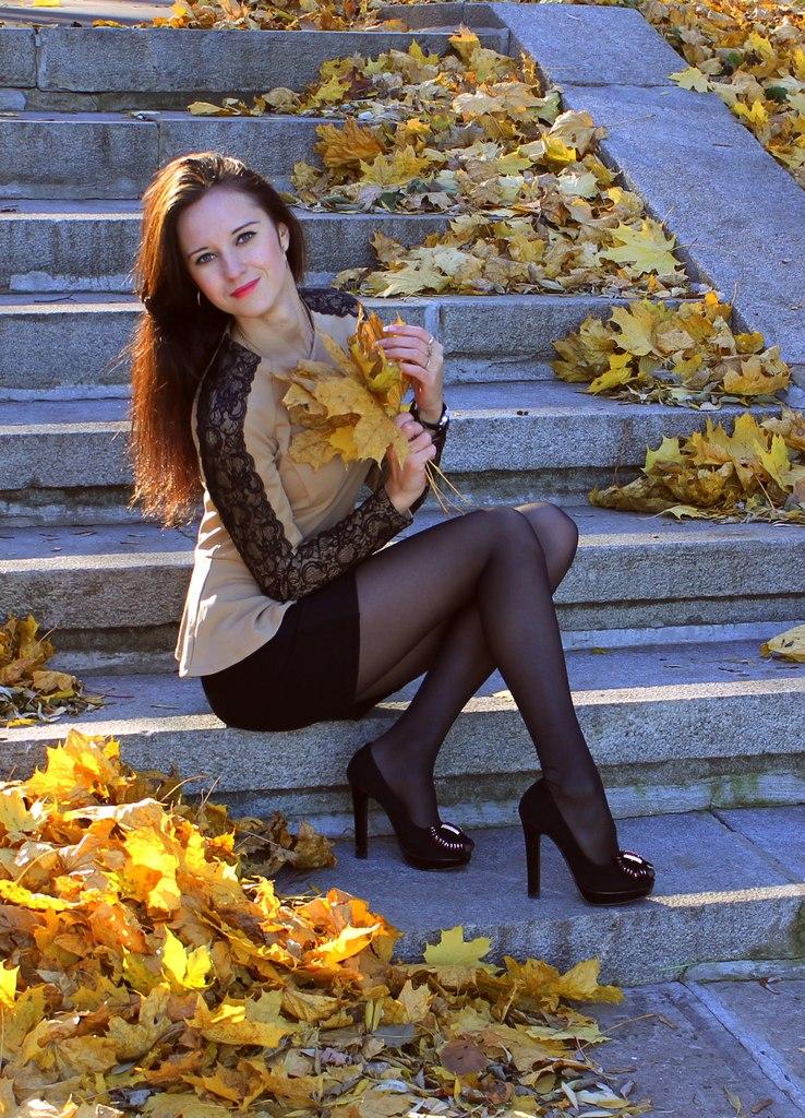 Красотка в осеннем парке на ступеньках