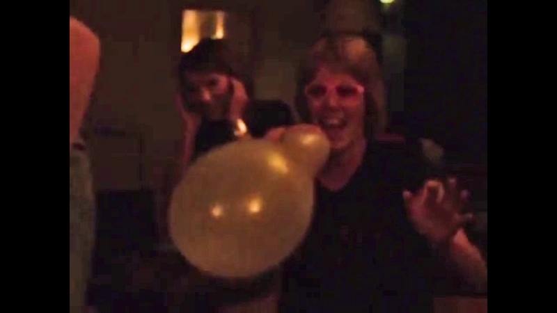 Girl blows to pop a balloon scaring the others