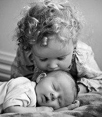 Сестричка целует маленького братика.  Черно-белые фото.