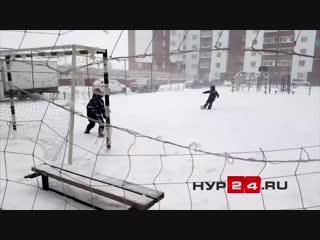 Дети играют в футбол в метель