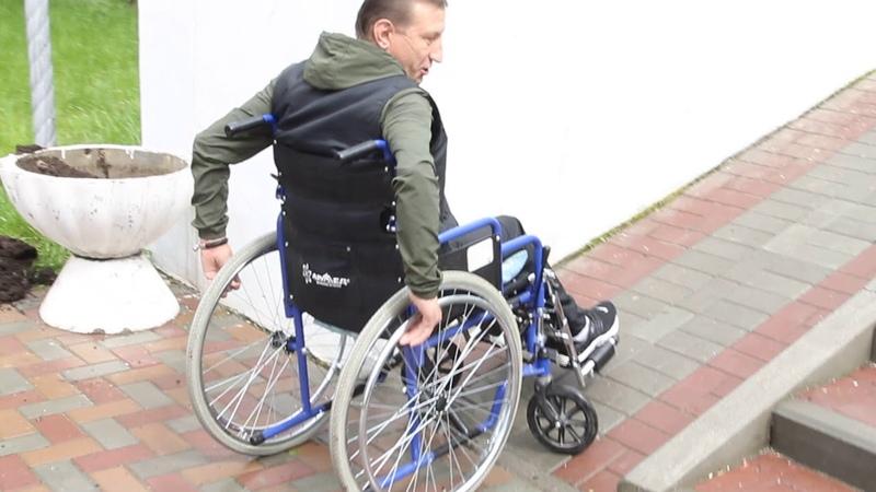 Сергей Константинов, инвалид-колясочник, показывает невозможность заезда на пандус за ДК БАЗа