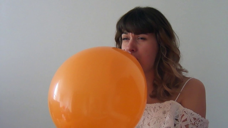 Blowing up an orange balloon caught this girl off guard when it suddenly pops