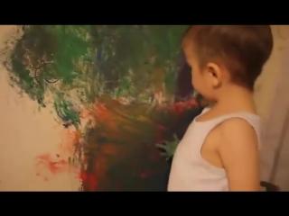 Мальчик рисует на стене красками.