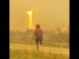 Очаровательная девушка-пожарный борется с огненным торнадо
