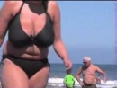 грудастая женщина идет по пляжу