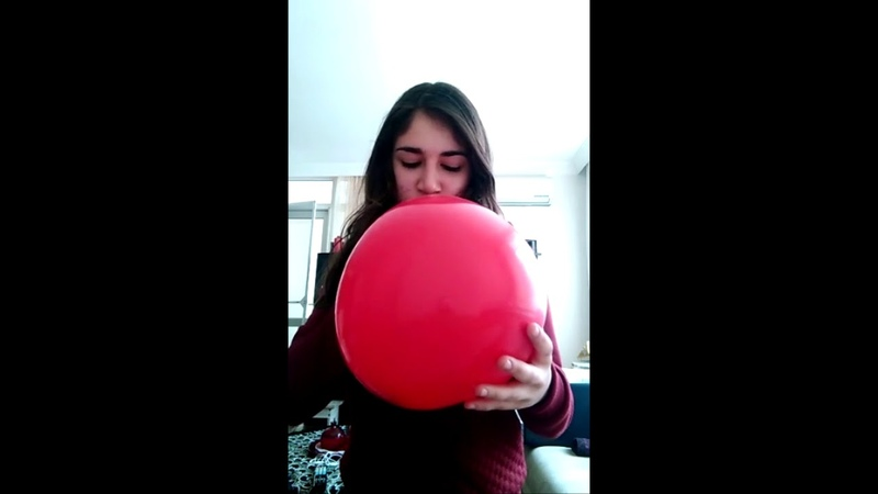 Lovely red heart balloon blow to pop girl