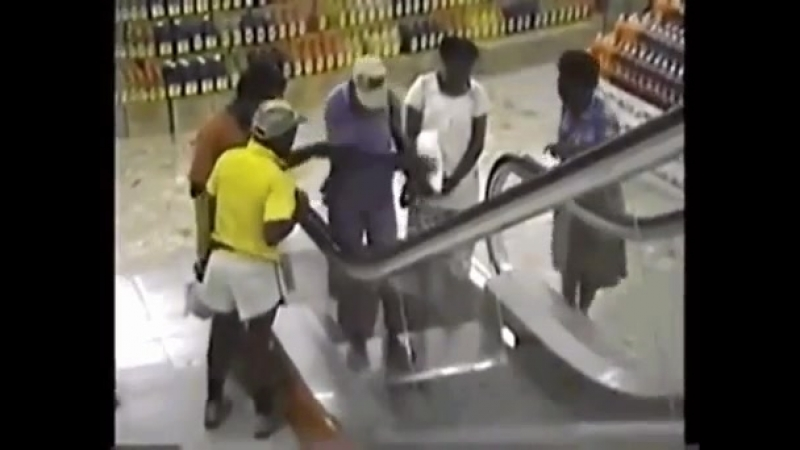 Man has never seen an escalator before so a couple of people help him out.