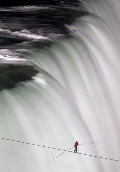 Канатоходец Ник Валленда прогуливается над Ниагарским водопадом.