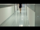 Woman in a black dress and high heeled shoes walking down the corridor of the office building
