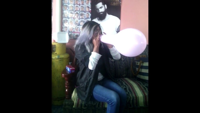 Silver hair girl blow to pops pink balloon