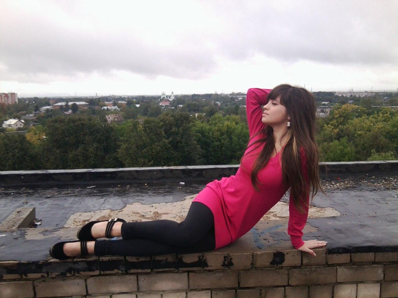 Девушка в красной тунике и черных леггинсах