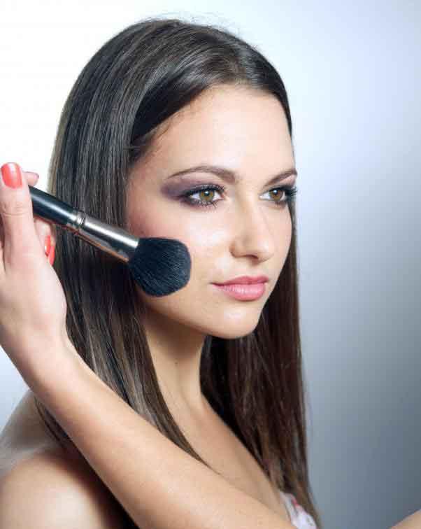 Косметолог применяет макияж к лицу женщины