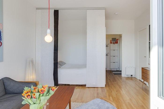 Зонирование квартиры-студии и гостиной-спальни японскими шторами.
