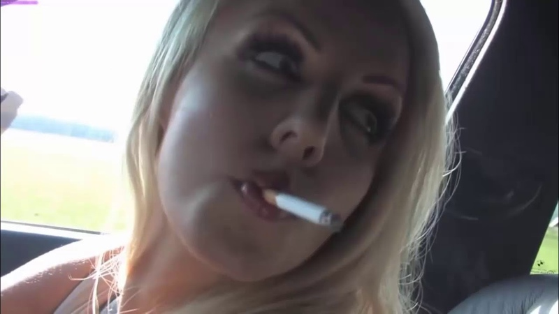 Sexy blonde woman smoking in her car.