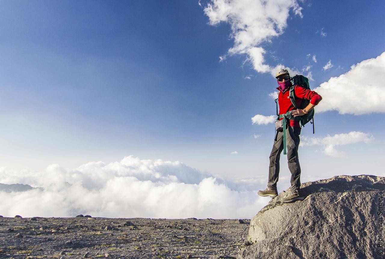 альпинист на фоне облаков на эльбрусе