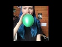 Blue haired girl blows up a teal balloon until it pops