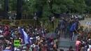 Momento en el que la caravana de migrantes rompe la valla fronteriza entre Guatemala y México