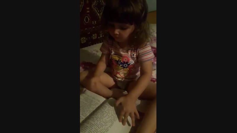 Карина читает книгу на Кар  непонятном языке