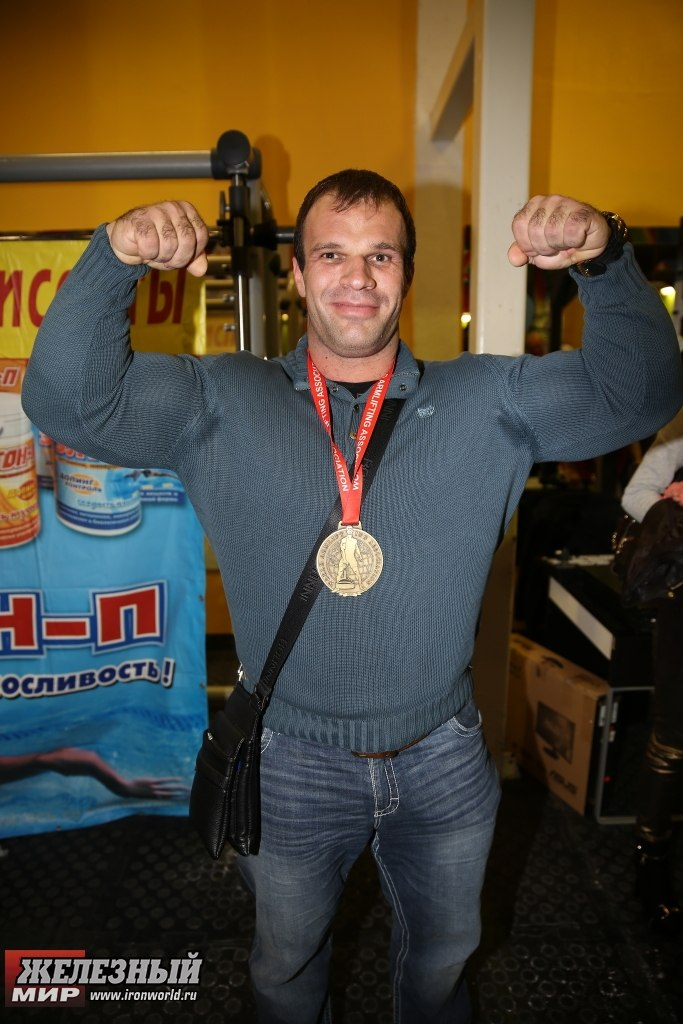 Denis Cyplenkov flexing his arms, with medal