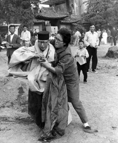 Женщина вырывает спички у буддийской монахини, облившей себя бензином.