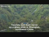 Tourists test their nerve on glass slide in Chinas Shangluo