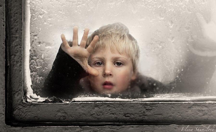 Вікно під час дощу, за ним дитина