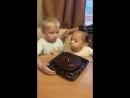 Кира дует на горящую свечку в торте
