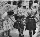 Любопытная итальянка живо интересуется кроем и фактурой ткани килта шотландских военных…