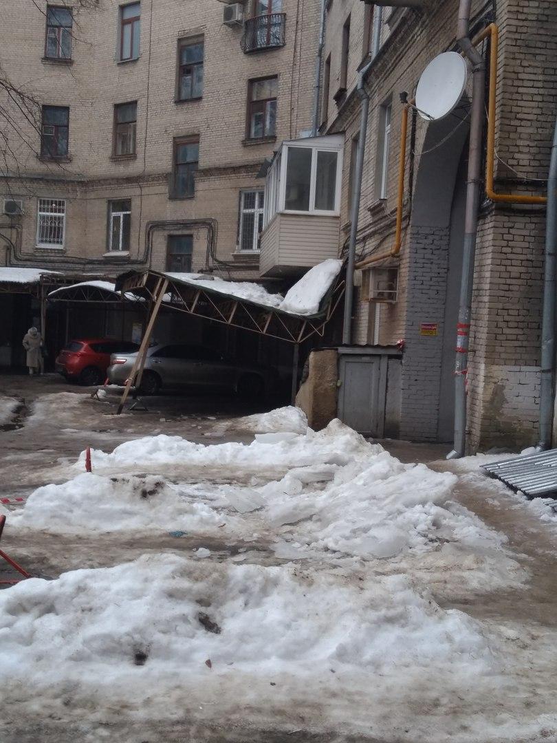 В Харькове во дворе дома под тяжестью снега прогнулся навес парковки (фото)