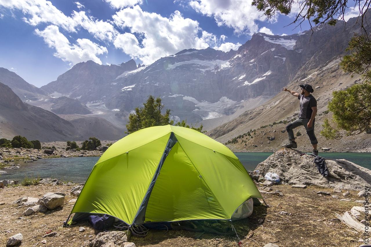 палатка на фоне озера и снежных гор, и парень показывает на горы