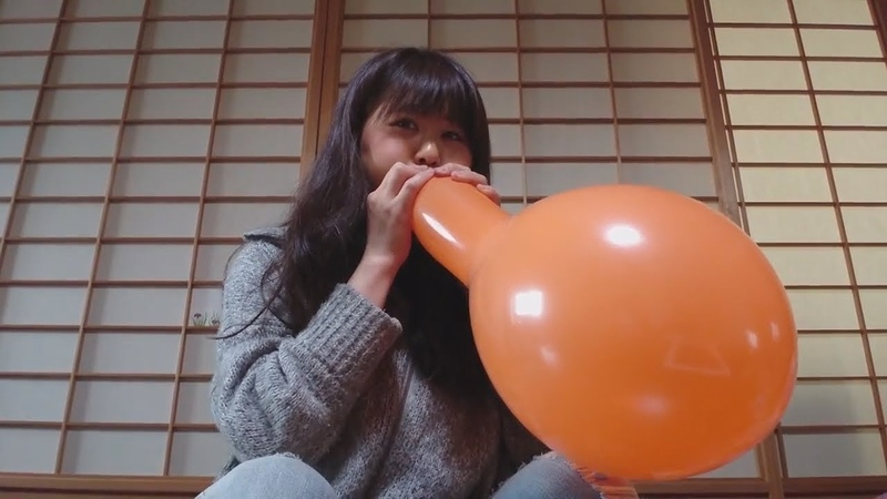 Cute japanese girl blows tight balloons and pops them
