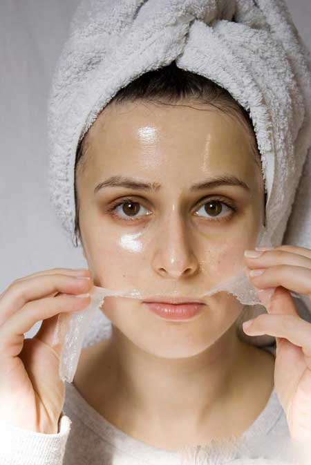 Женщина снимает отслаивающуюся маску для лица.