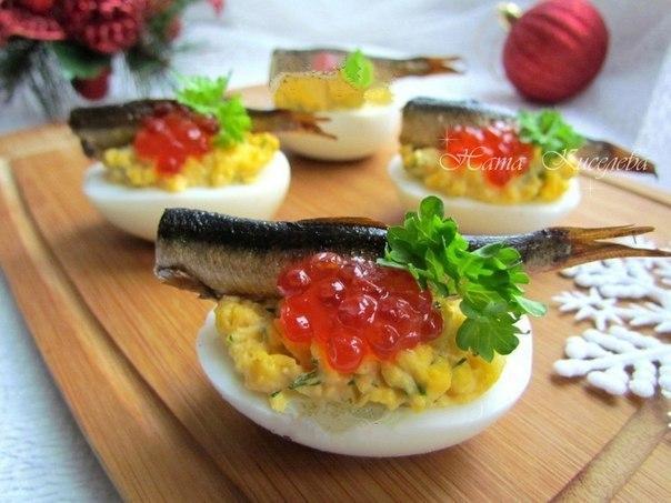 Фото: Фаршированные яйца со шпротами и красной икрой.<br><br>Вариантов приготовления фаршированных яиц очень много. Один из них - праздничный вариант со шпр