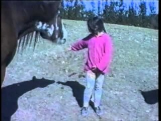 Girl hits horse, horse bites her hair and yanks her.