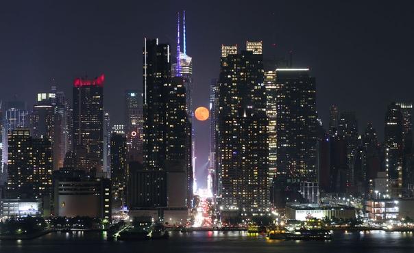 Луна поднимается над 42-й улицей в Нью-Йорке