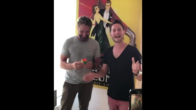 Gerard Butler is doing a magic trick with Rubik's Cube.