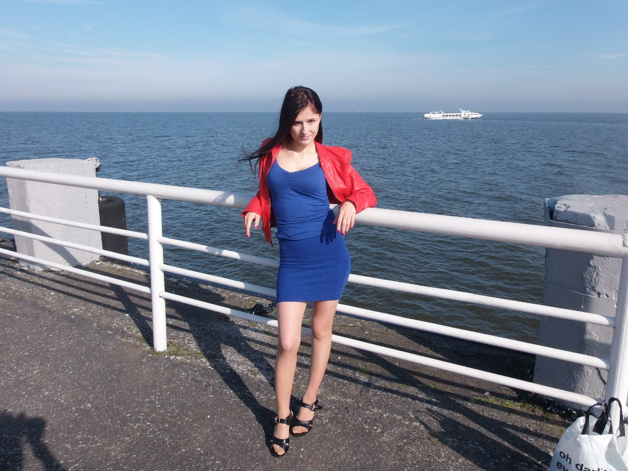 Стройная брюнетка на фоне реки в синем платье