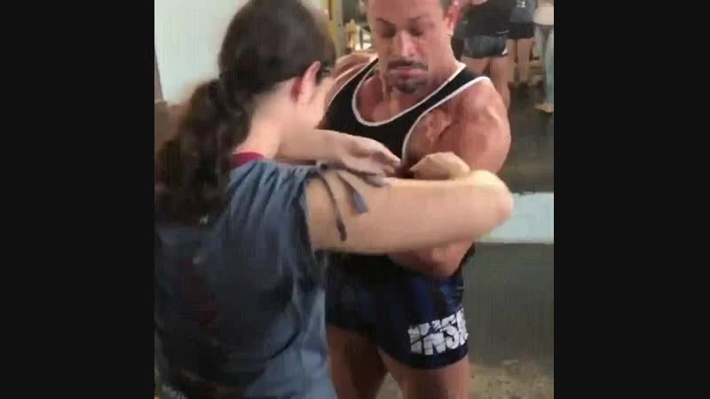 Guy lets blind girl at the gym feel his muscles, it puts the biggest smile on her face