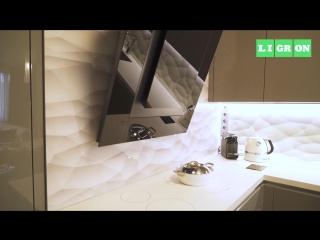 Современная кухня со столешницей из керамики Ligron Tech, вытяжкой с отделкой стеклом и стеклянными стеновыми панелями.
