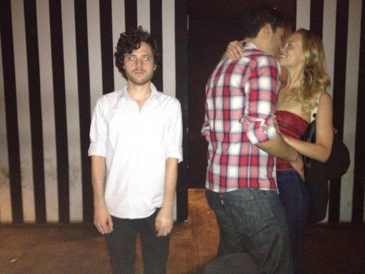 Парень фотографируется на фоне целующихся парочек