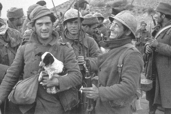 Джордж Оруэлл со щенком в руках в рядах ополченцев во время гражданской войны в Испании