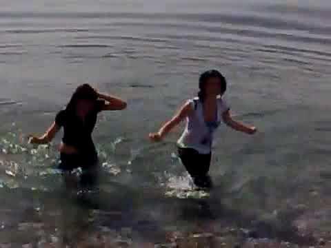Chicas se meten al mar con mezclilla y calcetines