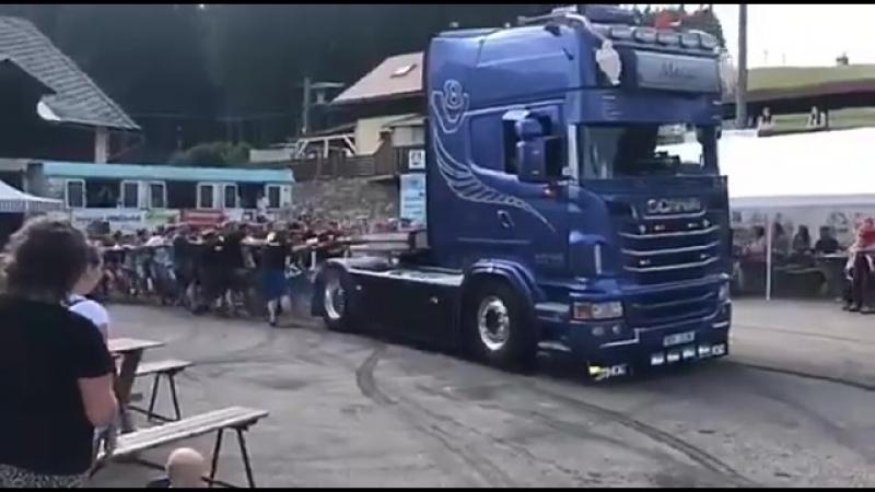Люди перетягивают грузовик.