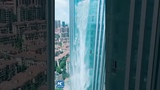Stunning waterfall cascading 100 meters down facade of building