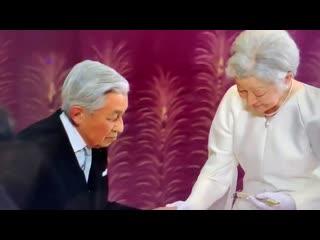 Император после отречения помогает жене спуститься со сцены