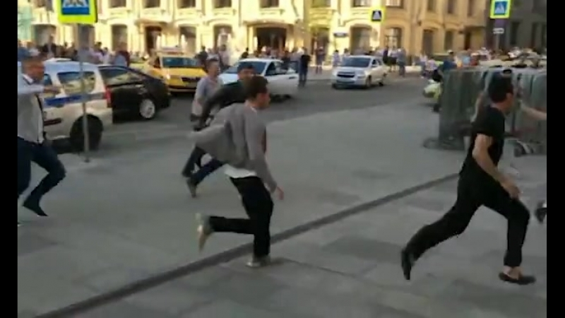 The Muslim taxi driver (pictured all in black) running away from the scene of the crash as bystanders chase him down the street