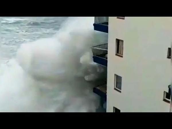 Гигантские волны достигают третьего этажа дома, сносят балконы, разрушают причалы, сносят машины.
