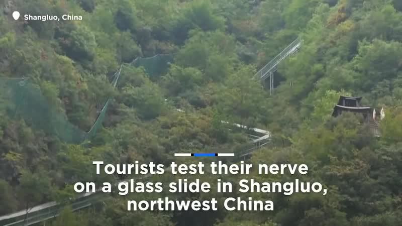 Tourists test their nerve on glass slide in China's Shangluo
